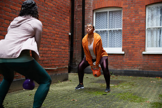 Picture of two women working out in their courtyard