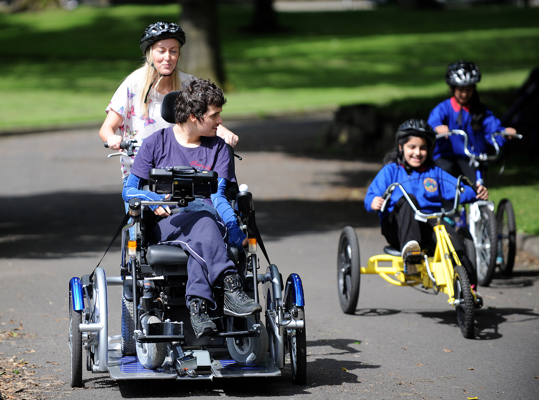 Young disabled people taking part in an adapted cycling session in the park