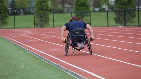 Back of a Man racing a wheelchair on a track
