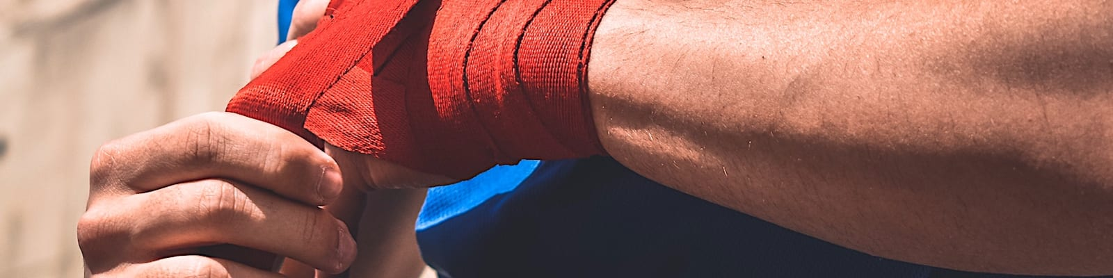 Man hold arm with red bandage on it