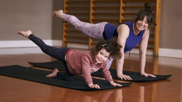 Mother and young daughter doing yoga