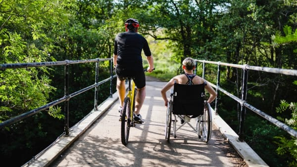 Cyclist and wheelchair user exercising in park setting together.