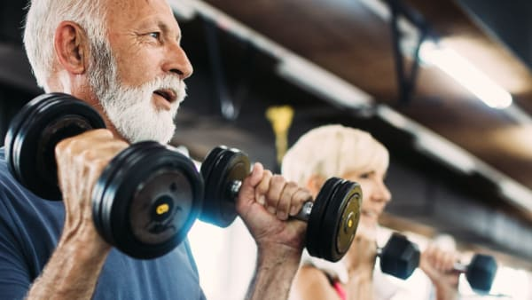 Older people using weights in a gym